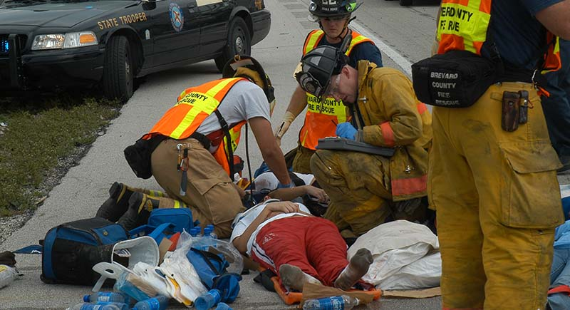 Firefighters performing emergency medical services on a person lying on the street.