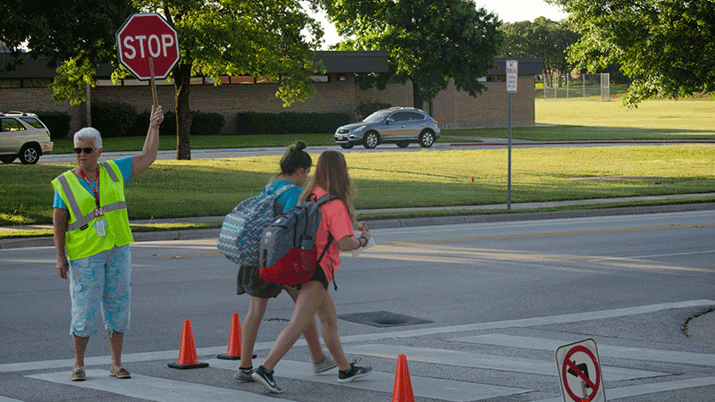 Crossing guard holding up a stop sign allowing 2 children with backpacks  to cross the street.