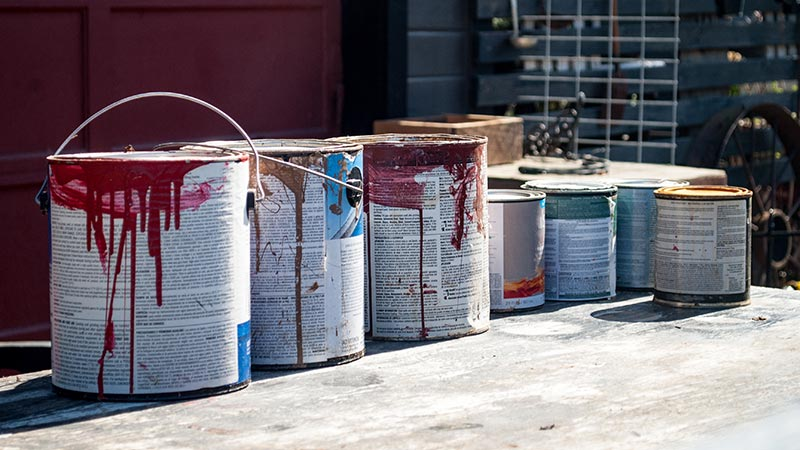 Multiple cans of used household paint.