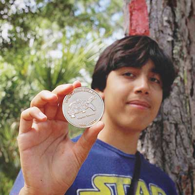 Young adult in a Star Wars shirt displaying the coin he found.