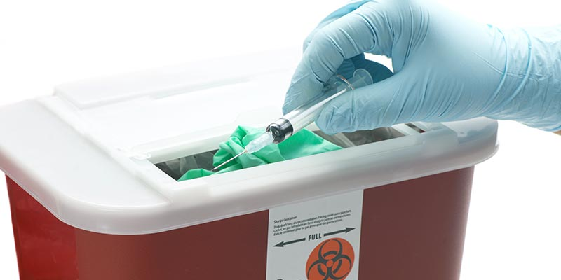 Gloved hand placing a used syringe into a sharpes disposal box.